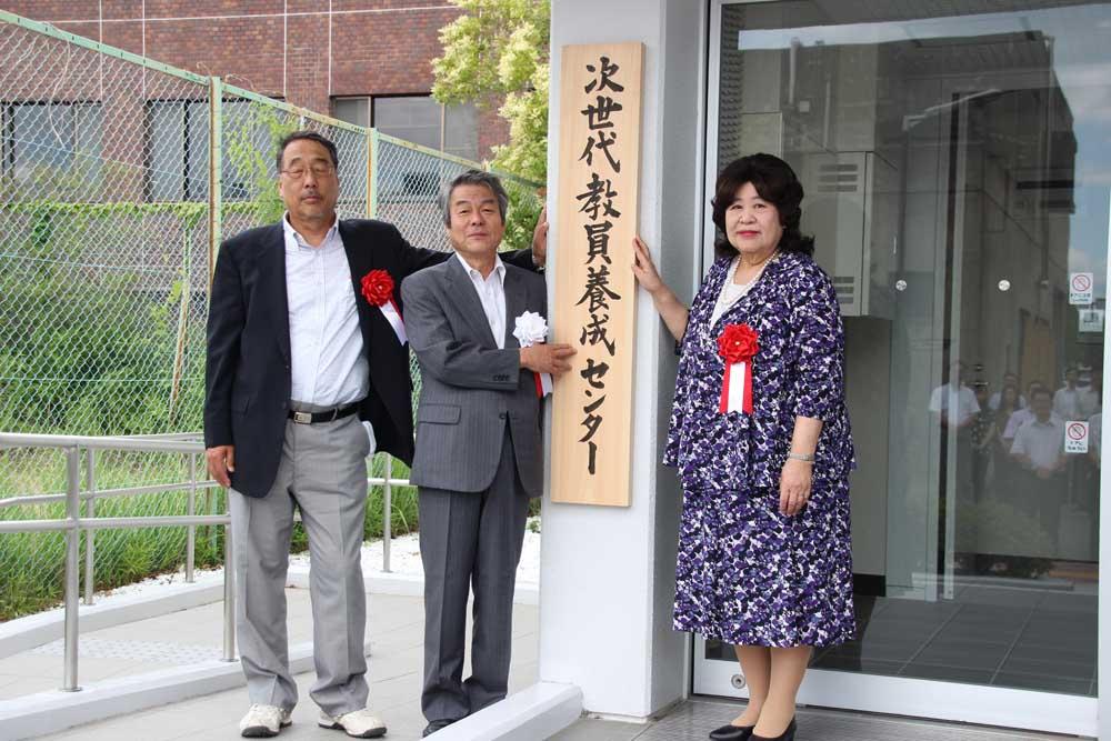 看板を前に記念撮影を行う、左から長尾大阪教育大学長、長友奈良教育大学長、位藤京都教育大学長