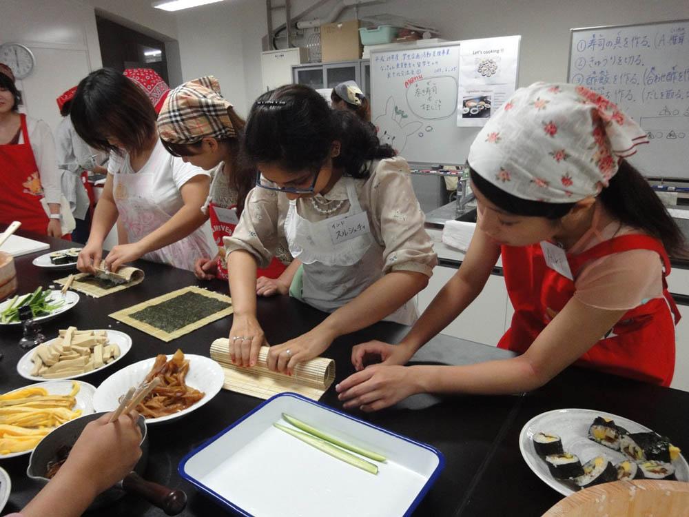 塾生と一緒に巻き寿司を調理する留学生